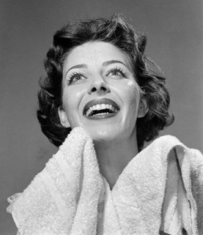 1950s smiling woman drying face with towel looking up